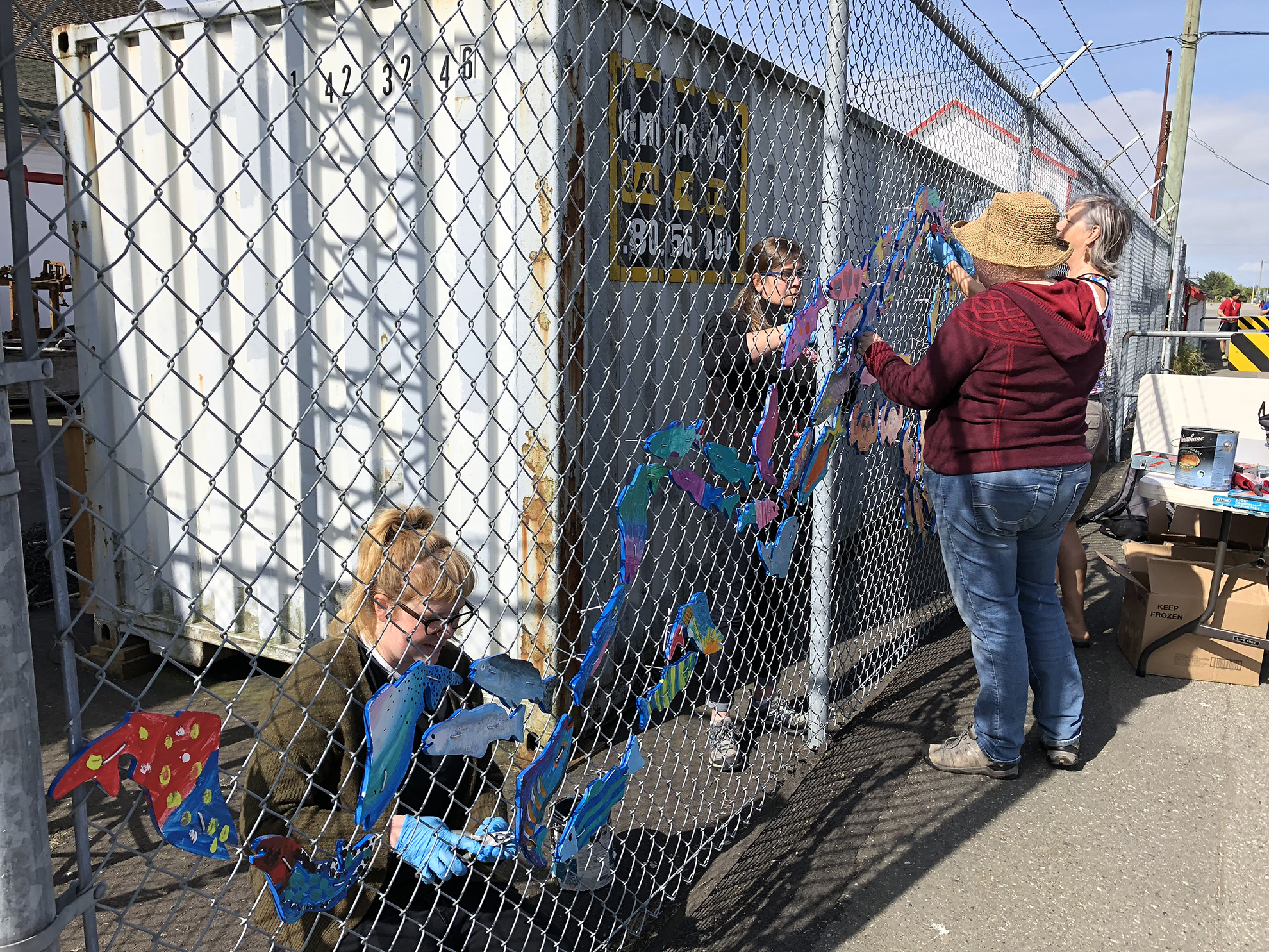 Stream of Dreams volunteers hanging up decorative fish art on fence