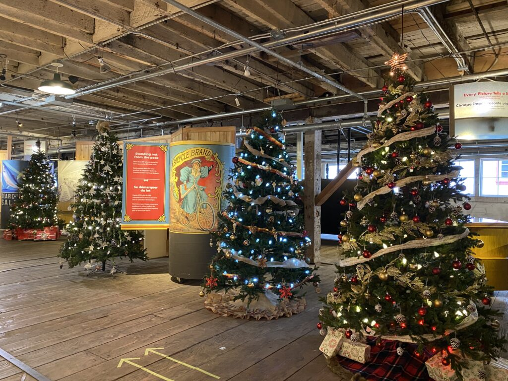 Four decorated Christmas trees on display inside historic cannery