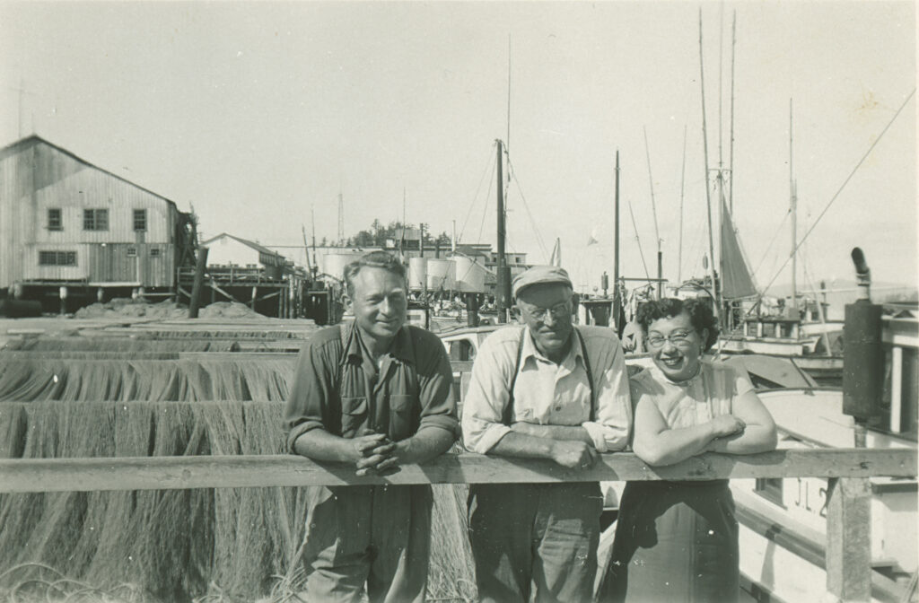 Two men and a woman in front of fishing nets at in front of harbour