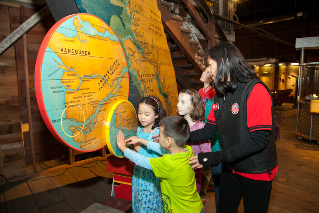 Heritage Interpreter and children in front of large map of BC.